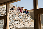 "Children outside of Kabul's ""Ring of Steel"" peek curiously into a CAI women's vocational center"