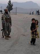 Armed guard for 3000 Cups of Tea film crew talks with a young girl and her brother in Kabul